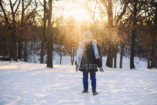 Boy standing in forest throwing snow in the air — Foto stock