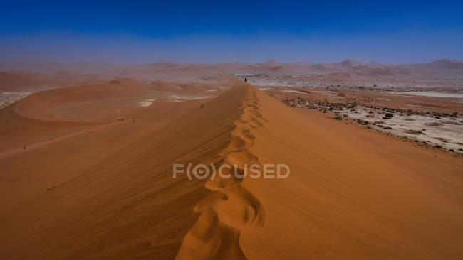 Далекий вид человека, идущего вдоль хребта песчаной дюны, Deadvlei возле Sossusvlei, Намиб Naukluft Национальный парк, Намибия — стоковое фото