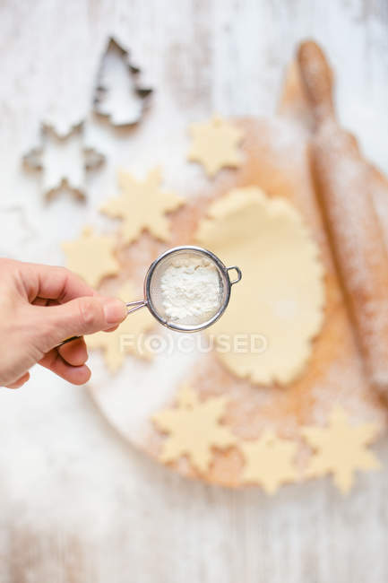 Cropped image of Woman hand sprinkling flour on Christmas cookie dough — Stock Photo