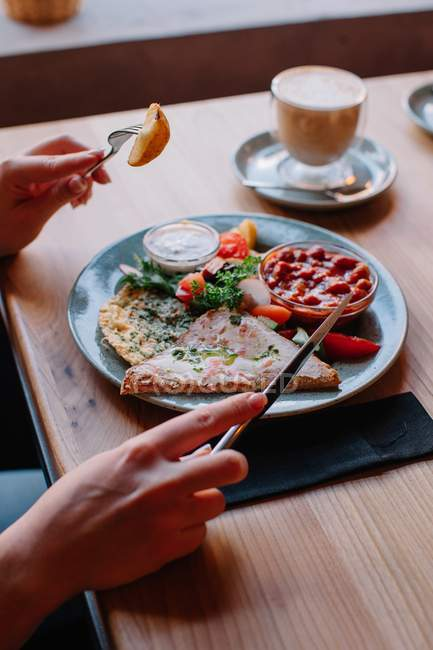 Woman eating an egg and bacon breakfast — стокове фото