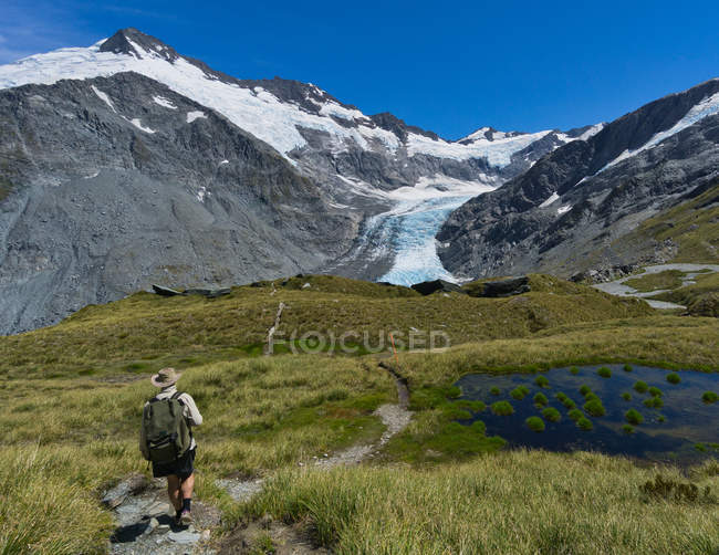 Man hiking on Cascade Saddle track, Mt Aspiring National Park, South Island, New Zealand — стокове фото