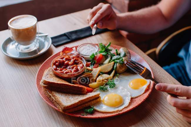 Обрізаний образ жінки їдять яйце і бекон сніданок — стокове фото