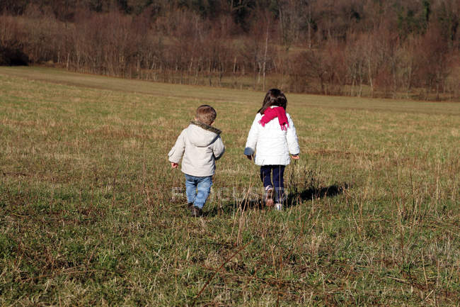 Ragazzo e ragazza che camminano in un campo insieme — Foto stock