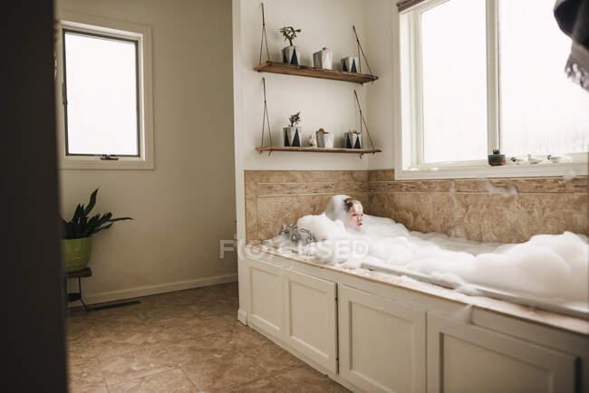 Ragazzo seduto in un bagno di bolle — Foto stock