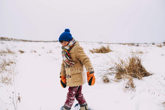 Menino andando na neve usando sapatos de neve — Fotografia de Stock