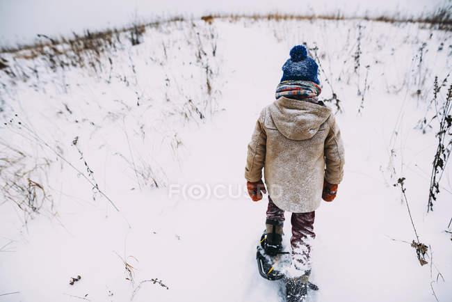 Мальчик ходит по снегу в снегоступах — стоковое фото