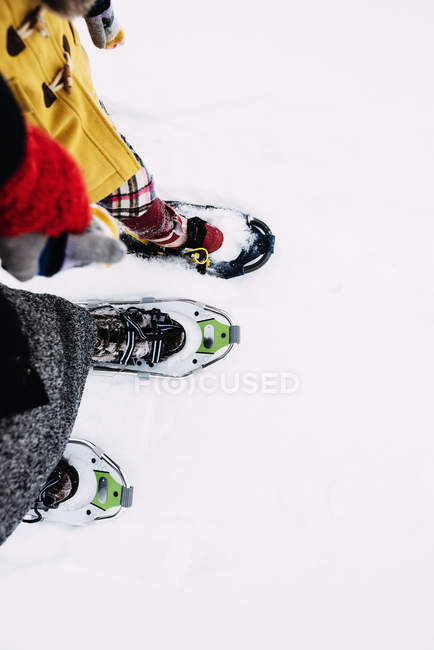 Cropped image of Mother and daughter snowshoeing — стокове фото