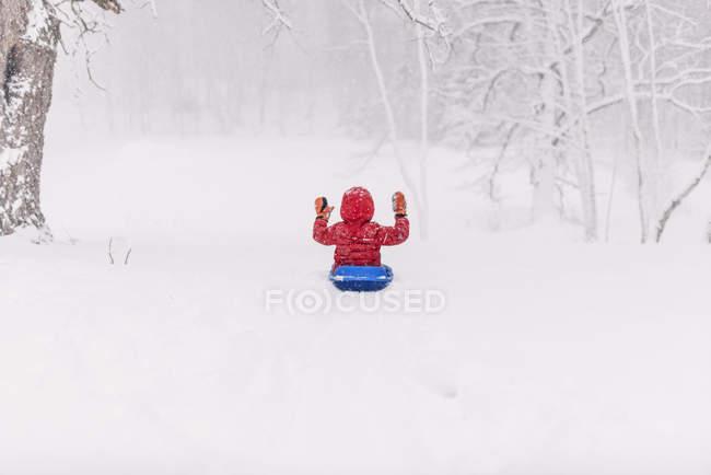 Мальчик катается на санках в снегу — стоковое фото