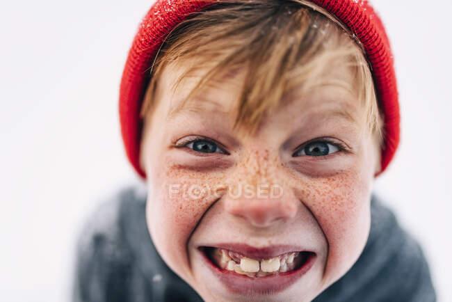 Portrait d'un garçon avec des taches de rousseur tirant des visages drôles — Photo de stock
