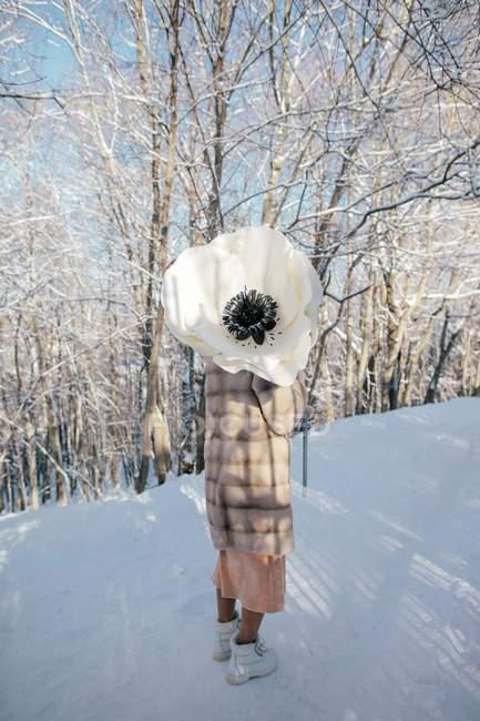Donna in piedi nella neve con in mano un enorme fiore di anemone artificiale — Foto stock