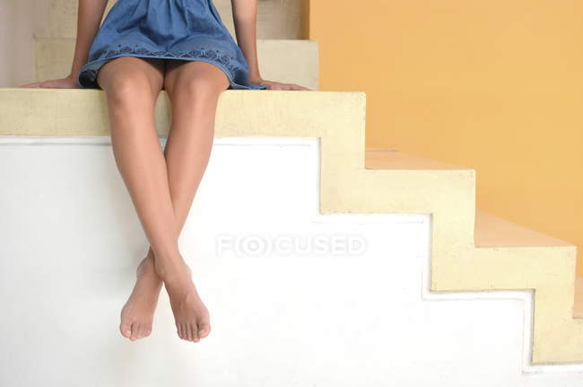 Cropped image of girl sitting on steps — Stock Photo