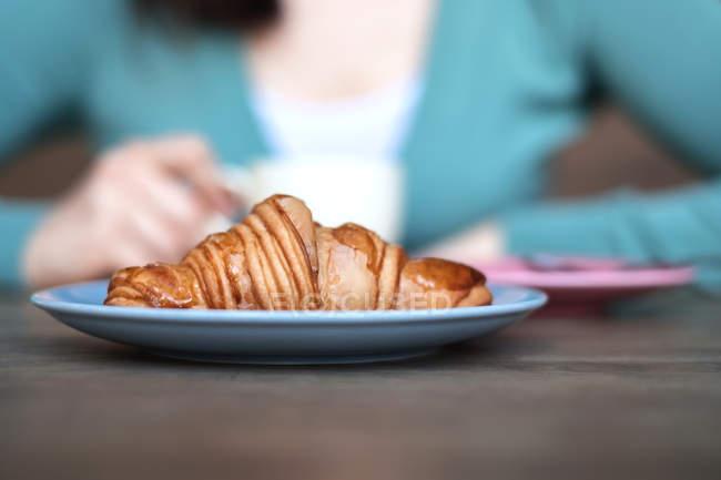 Croissant na frente de um café bebendo da mulher — Fotografia de Stock