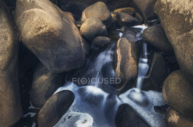 Closeup view of Water flowing through granite rocks — Stock Photo