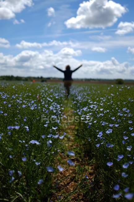 Silhouette di una donna in piedi in un campo con le braccia tese — Foto stock