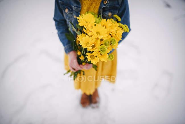 Девочка стоит в снегу, держа в руках букет цветов — стоковое фото