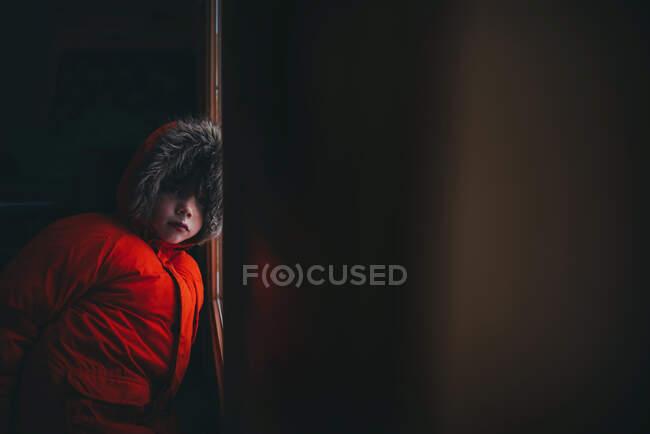 Мальчик в зимней куртке стоит у входной двери — стоковое фото