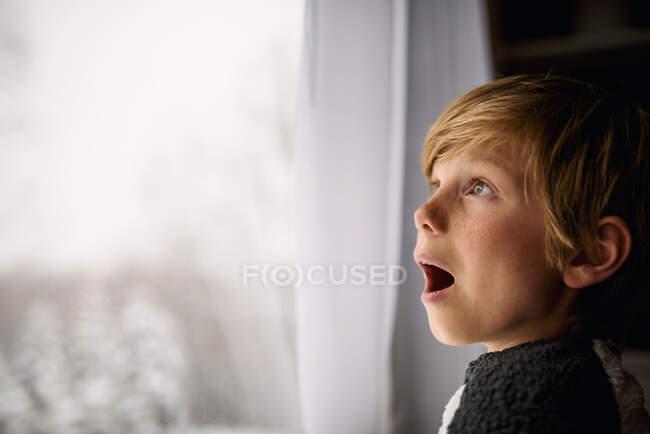 Удивлённый мальчик зимой смотрит в окно — стоковое фото