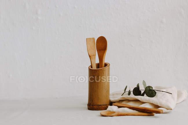 Set of wooden kitchen utensils, linen napkin and eucalyptus — Stock Photo