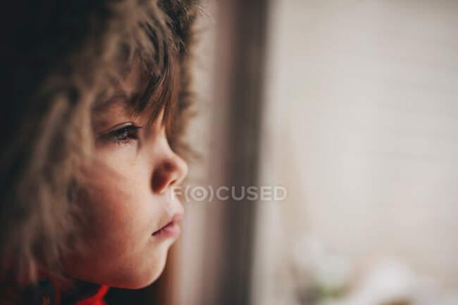 Мальчик в парке с мехом смотрит через стекло в дверь — стоковое фото
