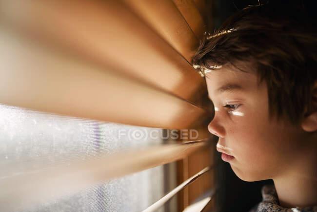 Мальчик стоит у окна и смотрит сквозь жалюзи — стоковое фото