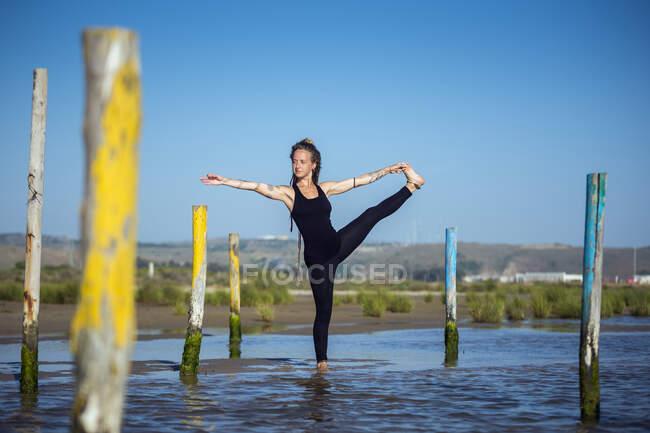 Женщина делает руку к большой позы yoga пальца на пляже, tarifa, cadiz, andalusia, Испания — стоковое фото