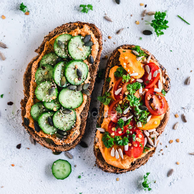 Paprika Hummus toasts with tomato and cucumber — Stock Photo
