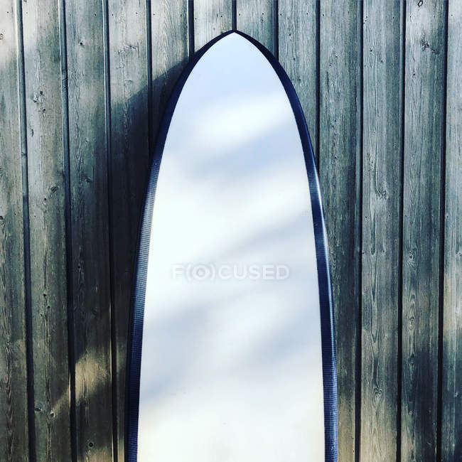 Close-up of a surfboard leaning against a wooden fence — Stock Photo
