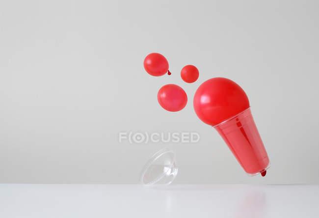 Bebida estilizada conceptual que se derrame de una taza desechable de plástico. - foto de stock