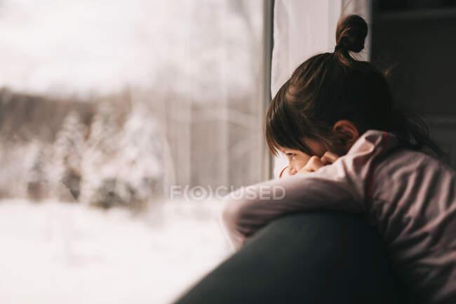 Девушка опирается на диван, глядя в окно — стоковое фото