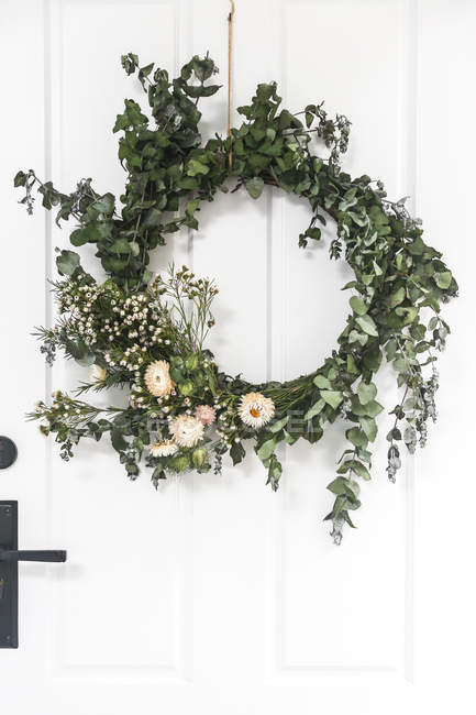 Christmas Wreath hanging on a white door — Stock Photo