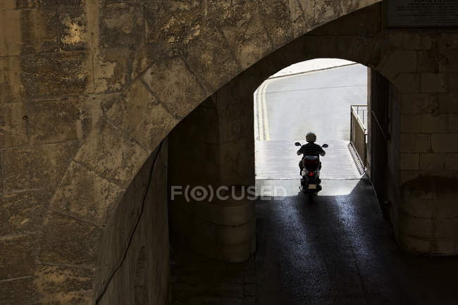 Uomo in moto attraverso il tunnel, cancelli Victoria, La Valletta, Malta — Foto stock