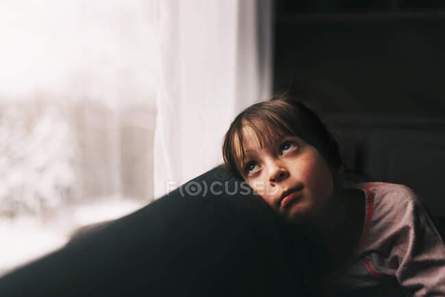 Девушка сидит на диване и смотрит в окно — стоковое фото