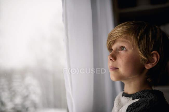 Портрет мальчика, стоящего у окна — стоковое фото