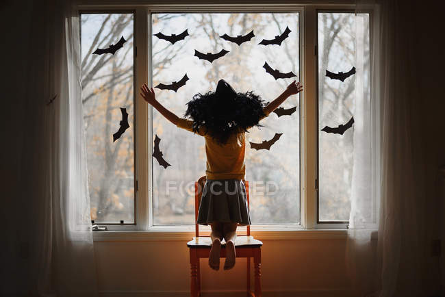 Girl wearing a witches hat kneeling on a chair by a window decorated with bats, United States — Stock Photo