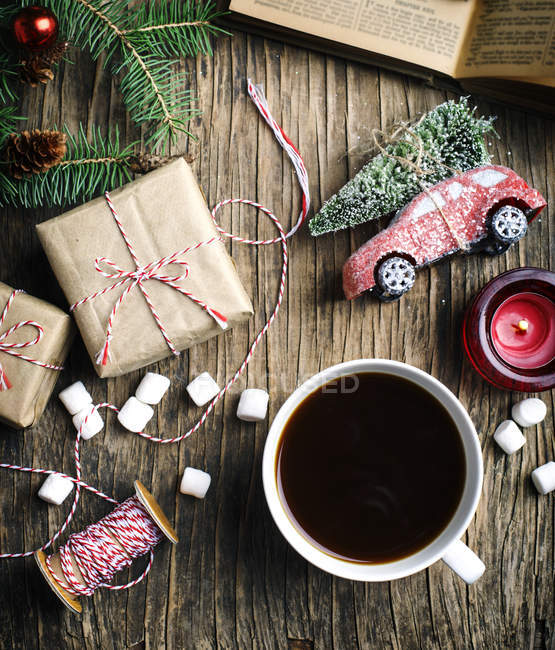 Cup of coffee, gifts and Christmas decoration, flat lay — Stock Photo