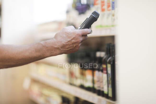 Asistente de ventas que utiliza un dispositivo digital para comprobar productos - foto de stock