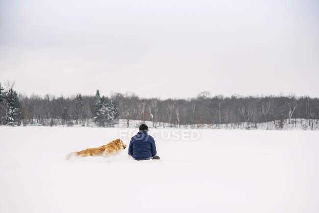 Homme assis dans la neige avec son chien golden retriever — Photo de stock