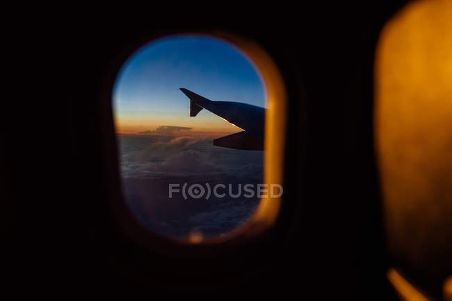 View of an airplane wing through the window at sunset — Stock Photo