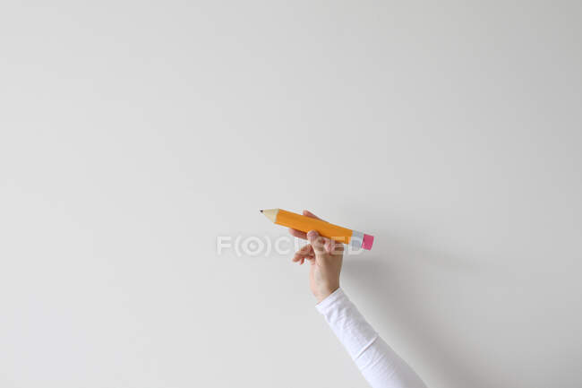 Woman's hand holding an oversized pencil — Stock Photo