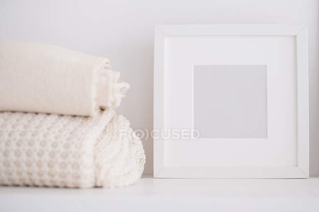 Picture frame and throws on a shelf — Stock Photo