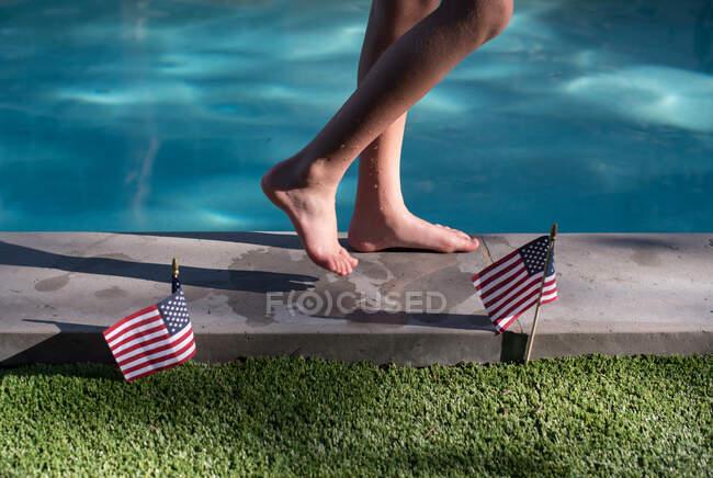Мальчик прогуливается по краю бассейна и американских флагов — стоковое фото