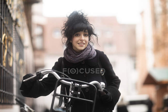 Frau steht mit Fahrrad auf Straße, Deutschland — Stockfoto