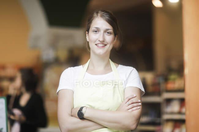 Портрет усміхненого продавця зі складеними руками. — стокове фото