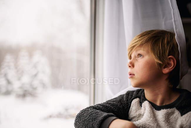 Мальчик зимой смотрит в окно — стоковое фото