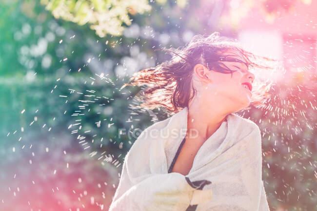 Ragazzo avvolto in un asciugamano scuotendo i capelli bagnati — Foto stock