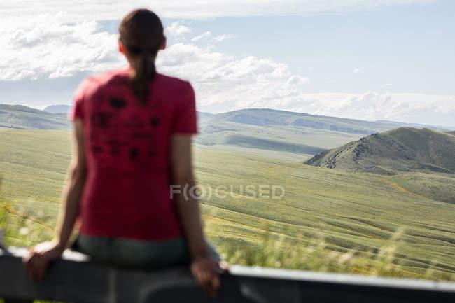 Donna seduta su una ringhiera guardando la vista, Lander, Wyoming, America, USA — Foto stock