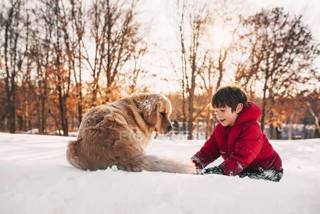 Menino brincando na neve com seu cão golden retriever — Fotografia de Stock