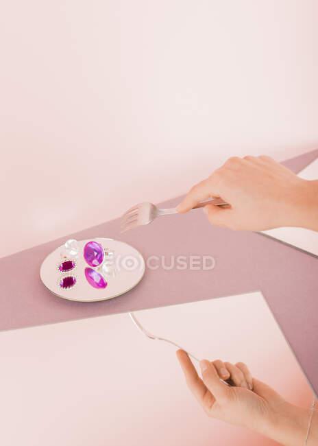 Mano de mujer sosteniendo un tenedor para comer algunas joyas - foto de stock
