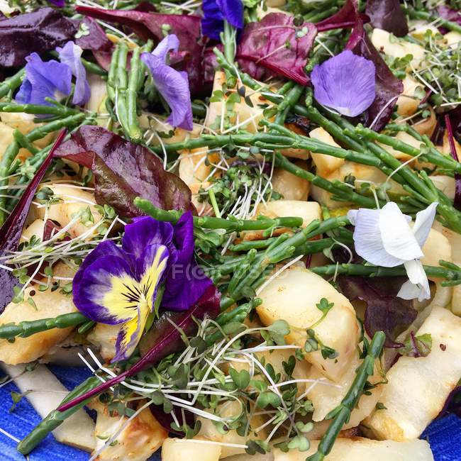 Baked celeriac with samphire and edible flowers — Stock Photo