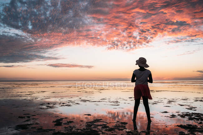 Silhouette di una ragazza in piedi sulla spiaggia al tramonto, Australia — Foto stock